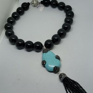 Large round onyx beads with detachable tassel.